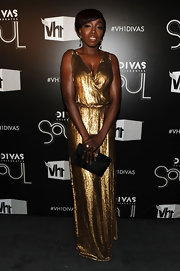 Estelle matched the glamour of her gold lamé gown with a black velvet clutch.