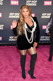 Lil Kim added extra oomph with a pair of black thigh-high boots.