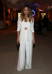 Chrissy Teigen was sleek and sophisticated in a white wide-leg pantsuit by Hayley Paige during the VIP sneak peek of go90.