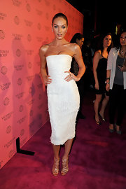 Candice Swanepoel accented her fitted white strapless dress with gold strappy gladiator heels.