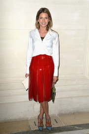 Helena Bordon gave her elegant blouse an edge with a red patent leather skirt featuring sexy see-through inserts.