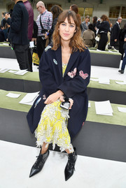 Alexa Chung sat front row at the Valentino fashion show wearing a butterfly-embroidered navy coat over a yellow floral dress.