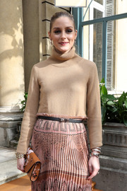 Olivia Palermo accessorized with a luxurious Bulgari Serpenti watch at the Valentino fashion show.
