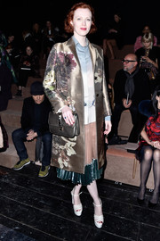 Karen Elson attended the Valentino fashion show looking elegant in a gold floral coat.