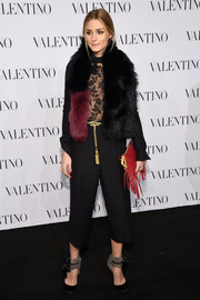 Olivia Palermo accessorized with a fringed red Valentino clutch for a spot of color to her black outfit.