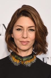 Sofia Coppola style her short hair with a deep side part and windblown waves for the Valentino Sala Bianca 945 event.