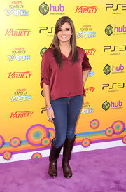 Rebecca Black opted for a more casual look, donning a black silk blouse paired with brown knee-high leather boots.