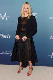 Molly Sims layered a black blazer over a sheer blouse for her Power of Women luncheon look.