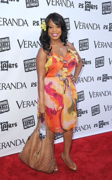 Niecy Nash teamed her tropical red carpet look with a tan leather shoulder bag with an imprinted logo.