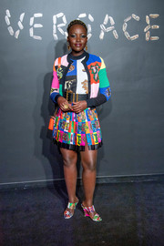 Lupita Nyong'o matched her cardigan with a graphic mini skirt.