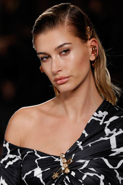 Hailey Baldwin wore her hair in a slick side-parted style at the Versace runway show.