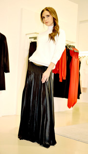 Victoria Beckham dressed up her casual top with a pleated black maxi skirt, also from her own label.