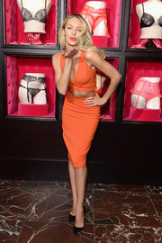 Candice Swanepoel flaunted her fit abs in a sexy orange cutout dress during Victoria's Secret's celebration of Bombshell's Day.