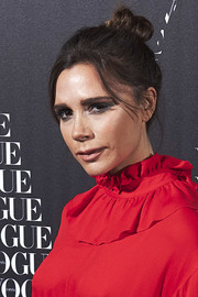 Victoria Beckham styled her hair into a mildly messy top knot for the Vogue dinner in Madrid.