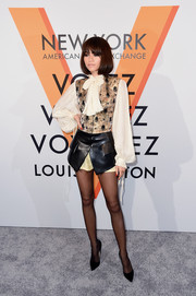 Zendaya Coleman paired a jacquard and leather vest with a white pussybow blouse, both by Louis Vuitton, for the 'Volez, Voguez, Voyagez' exhibition opening.
