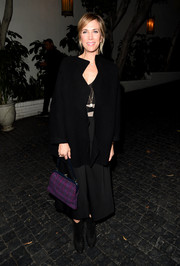 Kristen Wiig wore a simple black dress and coat that she matched with ankle boots for an understated look. The actress added a mix of color with her purple hued purse and a swipe of pink lipstick.