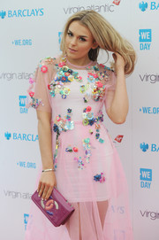 Tallia Storm paired a fuchsia patent clutch by Chanel with a flower-adorned dress for a sweet, colorful look during WE Day.