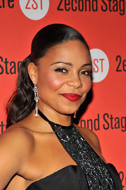 Sanaa Lathan added a swipe of rosy red lipstick to her look for a bold touch. A sleek ponytail and fluttering lashes completed her look.