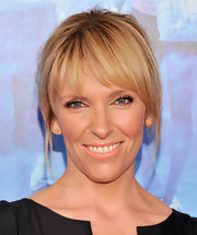 Toni Collette pulled back her blonde tresses into an updo that showed off her blunt bangs.