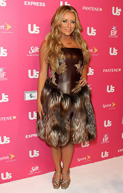 Aubrey O'Day wears a dramatic and controversial fur and leather dress. The corset of leather is embroidered with birds.