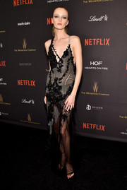 Daria Strokous donned a sheer, embellished chainmail halter dress by Versace for the Weinstein Company and Netflix Golden Globe party.
