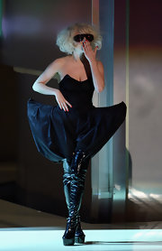 Lady Gaga completed her structured pants with patent leather knee-high boots.