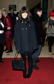 Claudia Winkleman added timeless luxury to her red carpet look with a jumbo Chanel flap bag. She paired the classic purse with an on-trend cape and ankle boots.