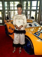 Andra Day completed her look with a pair of gold and black T-strap pumps.