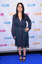 Abbi Jacobson donned a long-sleeved V-neck purple and green print dress with a cinched waist and midi hemline.