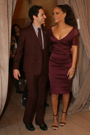 Rihanna showed her demure side in a burgundy cocktail dress by Zac Posen during the label's fashion show.