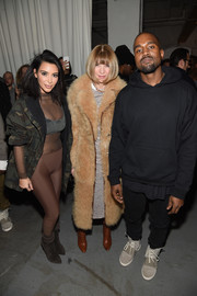 For her footwear, Kim Kardashian chose a pair of brown suede ankle boots, also by Yeezy.