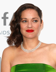 Marion Cotillard punctuated her look with a swipe of rich red lipstick.