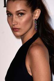 Bella Hadid accessorized with colorful dangling gemstone earrings when she attended the amfAR Cinema Against AIDS Gala.