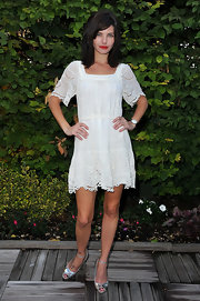 Delphine Chaneac was seen at the amfAR Inspiration Gala wearing a white day dress with crochet sleeves and hem.