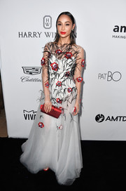 Cara Santana polished off her look with a metallic red clutch.
