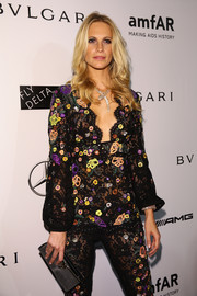 Poppy Delevingne paired a metallic silver clutch with a whimsical-chic floral pantsuit for the amfAR Milano Gala.