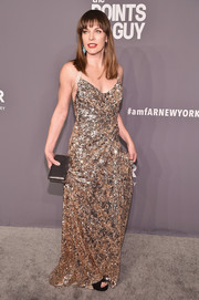 Milla Jovovich matched her dress with a bronze clutch.