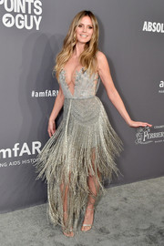 Heidi Klum shimmied on the gray carpet wearing a fringed silver gown by Paolo Sebastian at the 2019 amfAR New York Gala.