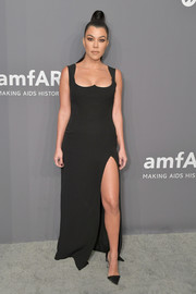 Kourtney Kardashian put on a sexy display in a black Versace gown with a high slit and a reverse sweetheart neckline at the 2019 amfAR New York Gala.