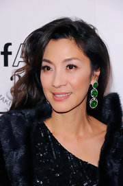 Michelle Yeoh added a glamorous touch of color to her sequined gown with tiered emerald green earrings.