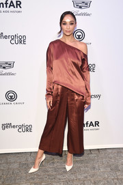Cara Santana was casual yet sophisticated in a loose bronze Tibi blouse, which she wore with one shoulder down, at the amfAR generationCURE Solstice 2017.