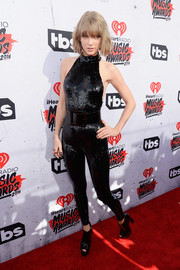 Taylor Swift looked dynamite in a sequined black halter jumpsuit by Saint Laurent at the iHeartRadio Music Awards.