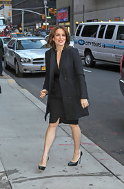 Tina Fay opted for a sophisticated work-appropriate ensemble, layering a gray wool coat over a demure black dress.
