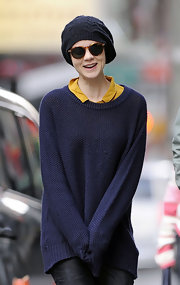 Carey Mulligan bundled up in a navy knit sweater layered over a collared mustard blouse.