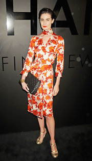 Erin O'Connor wore a below-the-knee long-sleeve cut-out wrap dress covered in orange floral print at the Chanel Bijoux De Diamant 80th Anniversary party.