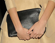 Alexa Chung paired her nude skirt suit with a classic, over-size, black clutch.