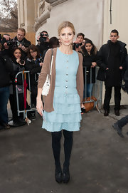 Laura Bailey toned down her frilly aqua dress with a brown cardigan.