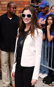 Anne Hathaway visited the 'Jon Stewart' show in NYC wearing a sleek white blazer with a black lapel.