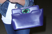 Ashley Greene brought some color to her denim ensemble with this purple leather handbag featuring an emerald green closure.