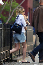 "Ashley Olsen heads out of her New York home in a super casual outfit that she jazzed up with a black and blue ""Boxwood"" shoulder bag. Her bag was cute but we can't keep her eyes off her little french pooch."